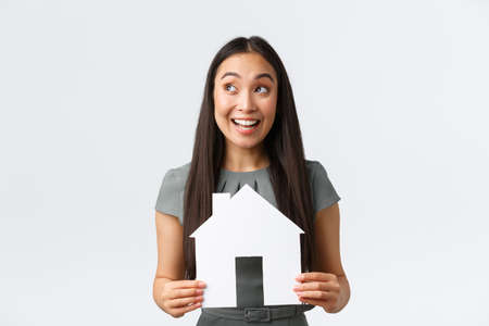 Insurance, loan, real estate and family concept. Smiling happy asian woman found perfect home, holding paper house and rejoicing, looking amused upper left corner at banner, white background