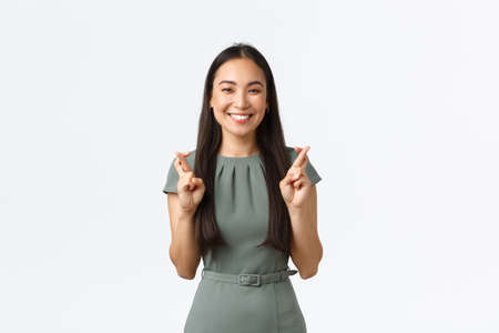 Small business owners, women entrepreneurs concept. Optimistic happy asian woman hope startup go well, cross fingers good luck and smiling, having faith, dream for wish come true