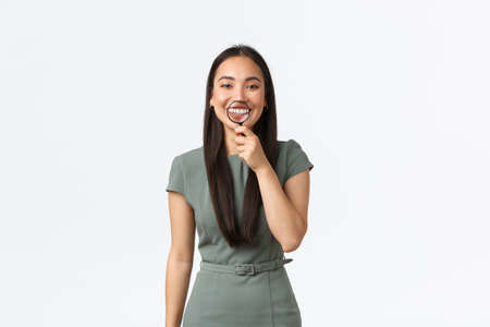 Healthcare, beauty and stomatology concept. Funny asian female with perfect white smile holding magnifying glass over teeth and grinning upbeat, standing white background