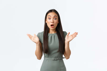Small business owners, women entrepreneurs concept. Surprised astounded asian female receive unexpected news, raising hands up and gasping shocked, react to announcement, white background
