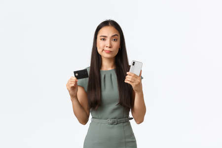 Small business owners, women entrepreneurs concept. Skeptical and unamused asian woman smirk displeased with reluctant expression, holding credit card with mobile phone, white background