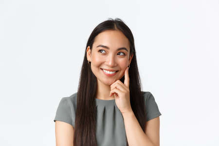 Close-up of creative and dreamy smiling pretty asian woman thinking, imaging something interesting in mind, looking left and touching cheek, pondering plan, standing white background