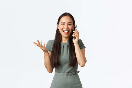 Small business owners, women entrepreneurs concept. Talkative happy attractive asian woman in dress, talking on mobile phone, discussing great news, looking surprised and joyful, white background Foto de archivo
