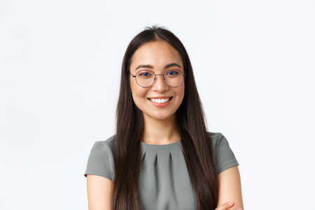 Small business owners, startup and e-commerce concept. Close-up of confident young businesswoman starting work in internet, wearing glasses, looking at camera with pleased smile