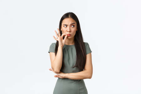 Small business owners, women entrepreneurs concept. Suspicious asian woman looking with disbelief upper right corner, feeling doubtful, zipping mouth, seal lips as making promise not speak