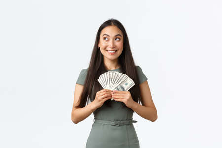Small business owners, women entrepreneurs concept. Dreamy excited, successful winning woman in dress thinking how invest or what buy while holding big sum of money, standing white background