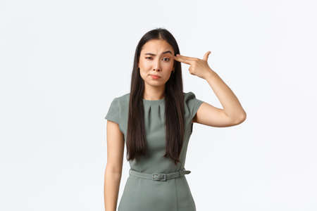 Small business owners, women entrepreneurs concept. Annoyed and tired asian businesswoman, employee shooting herself with fake gun gesture in head as fed up, standing white background
