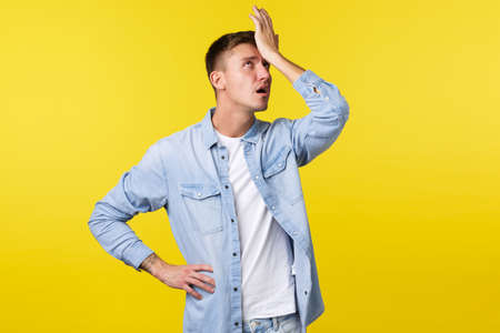 Lifestyle, people emotions and summer leisure concept. Annoyed and tired blond guy punch himself in forehead and roll eyes bothered, exhausted explaining something, yellow background Stock Photo