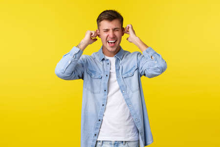 Lifestyle, people emotions and summer leisure concept. Distressed and annoyed handsome male student screaming pissed-off, shut ears with fingers, unwilling listen, standing yellow background