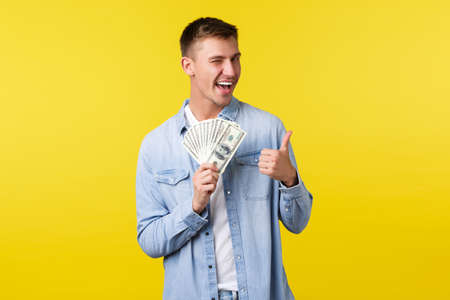 Investment, shopping and finance concept. Cheeky handsome blond man showing thumbs-up and winking, smiling as encourage give try lottery or casino, standing yellow background