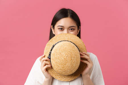 Beauty, people emotions and summer leisure concept. Close-up of shy and cute japanese girl cover face behind straw hat and smiling, standing pink romantic background and blushing coquettish