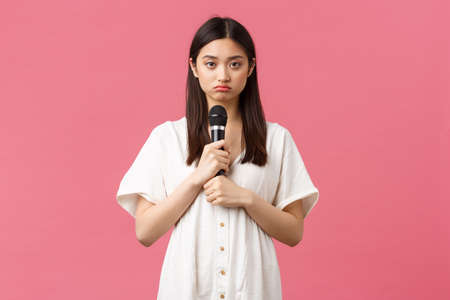 Leisure, people emotions and lifestyle concept. Gloomy and reluctant young asian girl holding microphone and looking sad camera, unwilling to perform, standing moody pink background