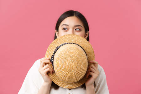 Beauty, people emotions and summer leisure concept. Close-up of dreamy beautiful asian girl hiding face behind straw hat and peeking left at promo banner, smiling with eyes, pink background 免版税图像