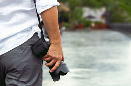 Man with photo camera Fashion Travel Lifestyle outdoor nature on sun light background. Foto de archivo