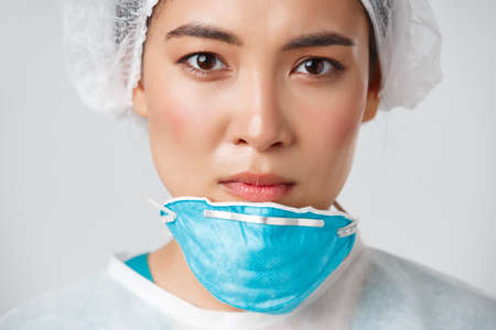 Covid-19, coronavirus disease, healthcare workers concept. Close-up of exhausted serious-looking asian female doctor take-off personal protective equipment, have skin damage from respirator