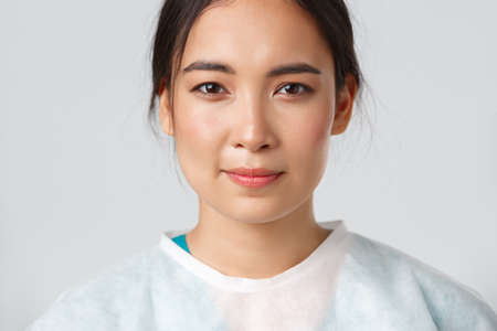 Covid-19, coronavirus disease, healthcare workers concept. Close-up of hopeful exhausted, smiling asian female doctor take-off personal protective equipment, have skin marks from respirator