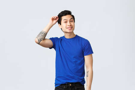 People different emotions, lifestyle and casual concept. Handsome asian queer guy in blue t-shirt, cute man brushing hair and smiling. Finally done haircut after self-quarantine during coronavirus Stock Photo
