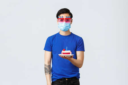 Different emotions, social distancing, self-quarantine on covid-19 concept. Young asian reluctant guy in funny glasses holding birthday cake with no emotions, hate celebrate home during pandemic