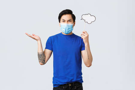 Lifestyle, people different emotions and covid-19 pandemic concept. Angry man in medical mask swearing and complaining, raise hand dismay, grimacing, holding comment cloud near head