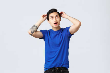 People different emotions, lifestyle and casual concept. Upbeat handsome asian man getting ready date, brushing hair, doing haircut and looking up cheerful, grey background