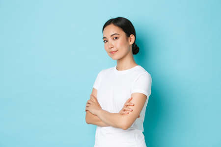 Portrait of happy and confident beautiful asian girl in white t-shirt cross arms chest and looking determined, standing half-turned over blue background, advertise product