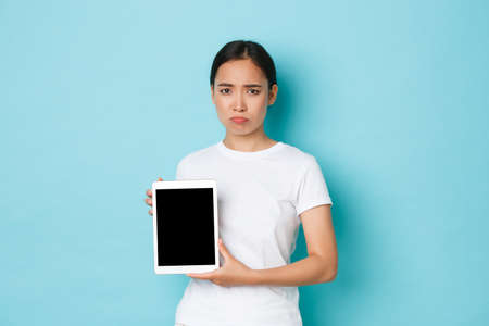 Portrait of sad and gloomy asian girl demonstrating chart or bad news on digital tablet screen, sulking uneasy, showing bad news, standing over light blue background disappointed Banque d'images