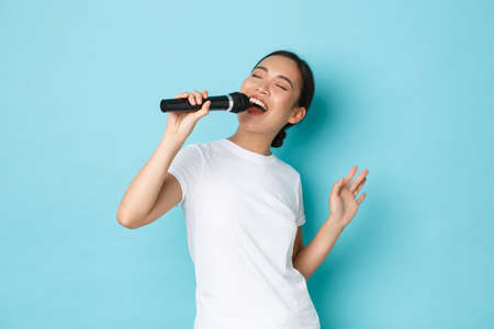 Lifestyle, people and leisure concept. Passionate and carefree pretty asian girl singing song in microphone, bending during performance, like going karaoke, standing light blue background performing Banque d'images