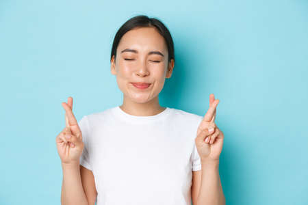 Close-up of happy dreamy young asian girl making wish, close eyes and hopefully cross fingers good luck, daydreaming, hoping for something good, anticipating news, standing light blue background