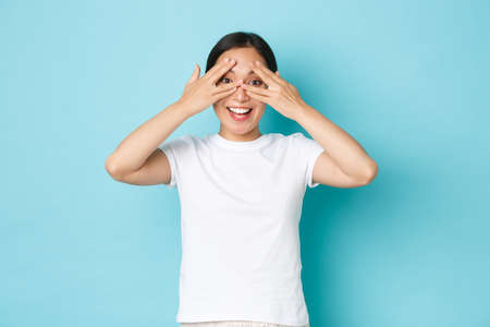 Carefree cute asian girl in white t-shirt looking through fingers, peeking at something interesting, curious whats going on, promised to not look, standing blue background