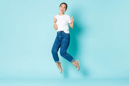 Fashion, beauty and lifestyle concept. Young cheerful asian girl enjoying shopping, looking upbeat and happy, jumping from happiness, showing thumbs-up and smiling over light blue background Foto de archivo
