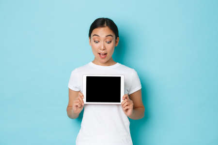 Excited and amazed beautiful asian female in white t-shirt looking at digital tablet screen with astonished, thrilled look, showing chart or demonstrate online shopping site, light blue background