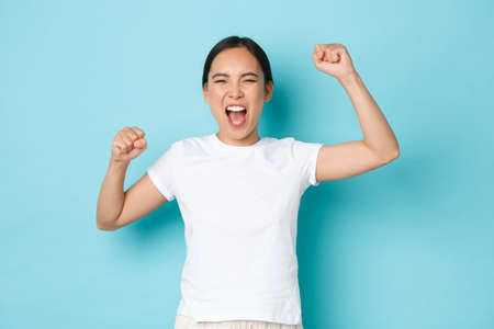 Rejoicing happy asian woman celebrating victory. Euphoric girl triumphing over achievement, fist pump and shouting yes delighted, standing encouraged and confident, blue background