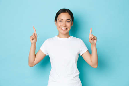 Gorgeous smiling young 20s female asian in casual clothes, pointing fingers up, showing advertisement, demonstrating promo offer. Korean girl indicating at banner, blue background Фото со стока