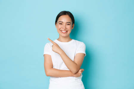 Cheerful confident asian girl in white t-shirt, pointing finger upper left corner and smiling delighted, showing way, advertising promo offer. Female student making her choice and demonstrating it