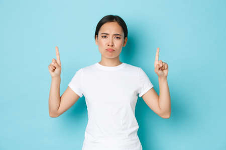 Upset and bothered asian girl in casual outfit, sulking disappointed, pointing fingers up displeased, complaining over bad quality, awful promo banner, standing blue background Stock fotó