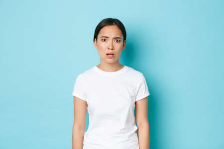 Lifestyle, beauty and shopping concept. Frustrated and shocked worried asian girl hear bad news, looking alarmed and nervous, feeling confused and stare at camera for answers, blue background Stock fotó - 153217625