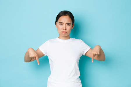 Disappointed and angry asian girl frowning, sulking upset while pointing fingers down, showing bad promo offer, complaining over advertisement, standing blue background dissatisfied