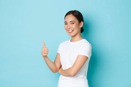Portrait of confident happy smiling, beautiful asian girl in white t-shirt showing thumb-up in approval, encourage do something, give permission, looking pleased over blue background Фото со стока