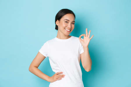 Portrait of sassy and confident pretty asian girl 20s in white t-shirt, guarantee everything under control, showing okay gesture, approve or like product, winking encouraging, blue background
