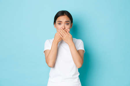Shocked and worried asian woman in white t-shirt gasping, cover mouth and looking ambushed with bad concerning news, standing terrified and anxious over blue background Stock fotó - 153218070