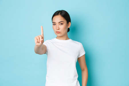 Serious-looking assertive young asian woman forbid action, express strong disapproval or disagree, shaking finger in warning sign, prohibit something bad, looking displeased and confident