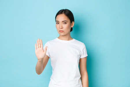 Serious confident asian woman stop something bad, raising hand in prohibtion, disagree or forbid gesture, standing blue background and refuse bad offer, rejecting