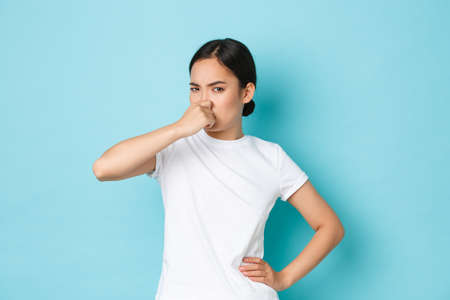 Disgusted and bothered asian girl complaining on bad smell, cover nose and grimacing from reek, awful stink, standing displeased and annoyed over blue background. Copy space Stock Photo