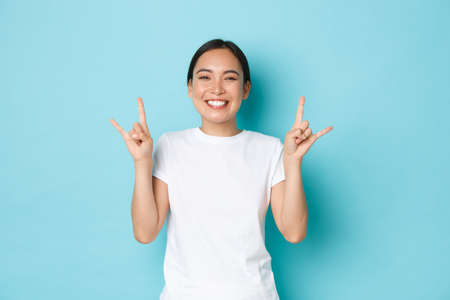 Carefree funny and upbeat pretty asian girl in white t-shirt, showing tongue and rock-n-roll gesture, enjoying awesome festival, looking pleased and amazed, partying over blue background