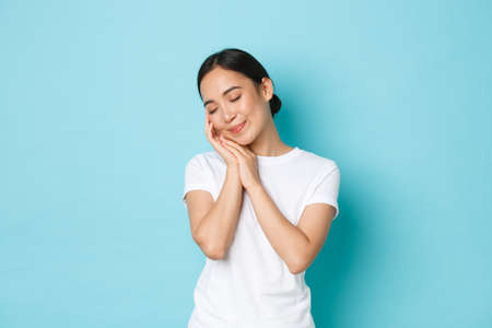 Beauty, fashion and lifestyle concept. Portrait of smiling romantic asian girl close eyes and tenderly touching face with hand, leaning on palm, daydreaming, standing blue background. Фото со стока