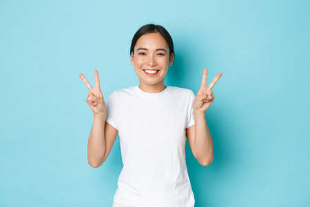 Beauty, fashion and lifestyle concept. Portrait of beautiful asian girl in white t-shirt standing over blue background, smiling and showing kawaii peace gesture, sending positivity and joy Фото со стока