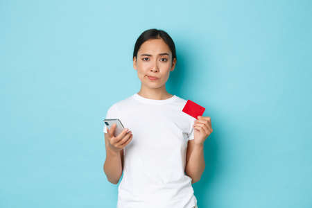 E-commerce, shopping and lifestyle concept. Skeptical and doubtful asian girl looking displeased, smirk while holding smartphone and credit card, unsure about safety of internet transaction Фото со стока
