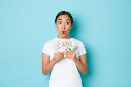 Shopping, money and finance concept. Excited happy asian girl showing cash of dollars and rejoicing, earn fist paycheck, receive salary or raise, standing upbeat over light-blue background
