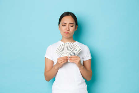 Shopping, money and finance concept. Concerned and perplexed asian girl looking at cash of dollars with puzzled, indecisive expression, making decision over light-blue background