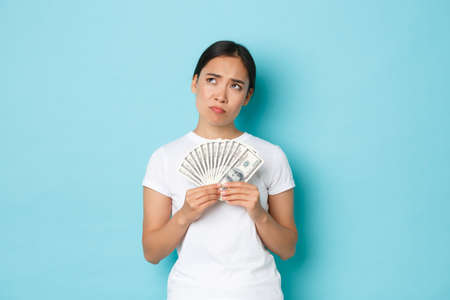 Shopping, money and finance concept. Thoughtful and creative pretty asian girl thinking where invest money, holding cash and looking upper right corner, making choice, deciding what buy